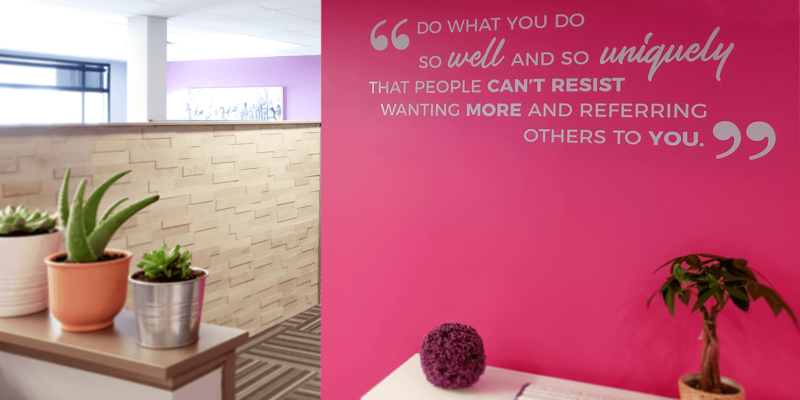 Pink office wall with a quote: Do what you do so well and so uniquely that people can't resist wanting more and referring others to you
