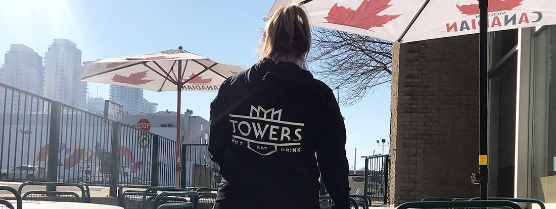 university student wearing a custom-made hoodie with MacEwan Towers logo