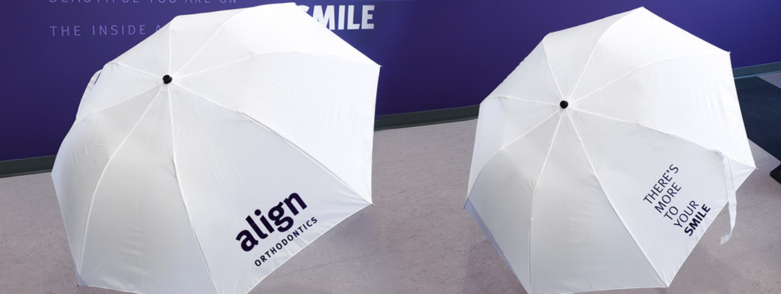 branded umbrellas showing the client's logo and their tagline