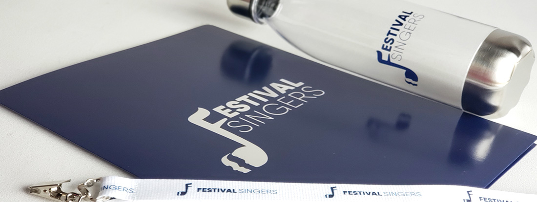close up of the logoed water bottle, lanyard and a folder for a welcome package